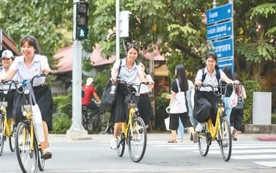 2017年8月15日,在泰国曼谷的泰国国立法政大学,学生们使用ofo小黄车出行。 新华社记者 李芒茫摄
