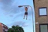瑞典消防员赤膊爬上路灯杆表演引体向上