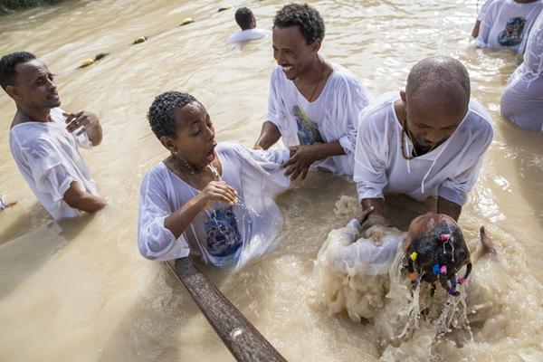 约旦河西岸朝圣者在泥水中受洗 庆祝主显节