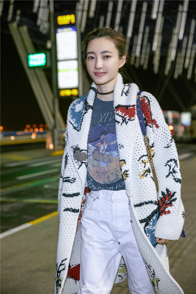 王丽坤俏皮现身上海机场 素色穿搭清新自然