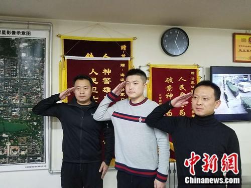 """三位民警重现当天""""对监控敬礼""""的情形。左起:李克、乔宇、刘志远。 冷昊阳 摄"""