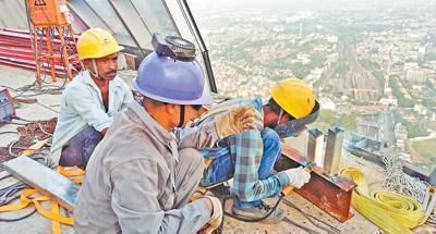中国和斯里兰卡工人在莲花塔观光台上施工。   本报记者 苑基荣摄