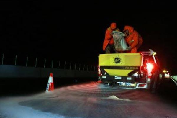 连接黔桂高速桥面结冰 护路工人连夜撒盐除冰