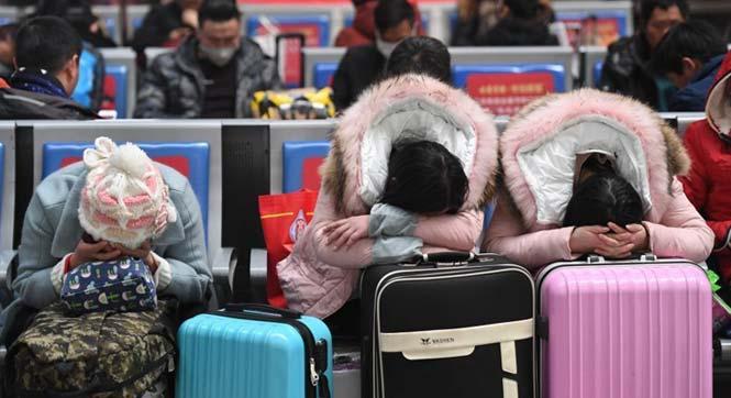 春运启幕 旅客趴行李箱上打盹