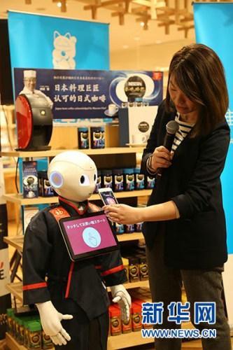 """2月8日,在日本东京的""""机器人拜年咖啡厅"""",工作人员演示使用支付宝程序和机器人互动。新华社记者 钱铮 摄"""
