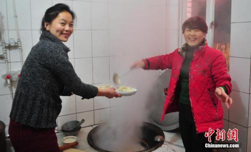 资料图:辽宁省葫芦岛市民在家中与家人享受丰盛的年夜饭。中新社发 于海洋 摄