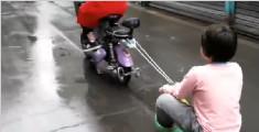 亲妈?实拍女童坐滑板车 女子骑电驴绳拖