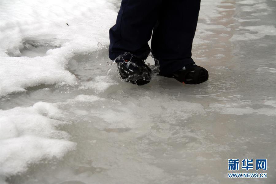 2月27日,在挪威朗伊尔城,一名行人走过冰雪融化的路面。新华社记者梁有昶摄