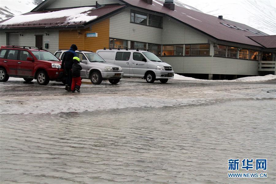 """2月27日,在挪威朗伊尔城,两名行人走过冰雪融化的路面。  就在欧洲大部分地区突遇寒冬之际,全球最北小镇朗伊尔城却经历异乎寻常的北极""""高温""""天气。朗伊尔城位于挪威属地斯瓦尔巴群岛的最大岛──斯匹次卑尔根岛,地处北纬78度,距离北极点只有1300公里。然而,在这个号称全球最北的小镇,26日当天的白天气温却高达零上4摄氏度,夜间也未突破冰点。在正常情况下,该城2月的平均气温为零下18摄氏度左右。  新华社记者梁有昶摄"""