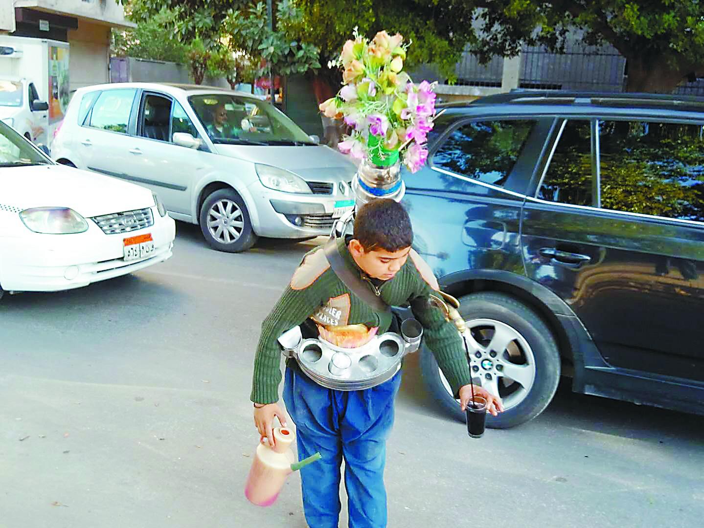 腰間斜挎大水壺 負重二十多公斤 開羅少年插着玫瑰花賣水