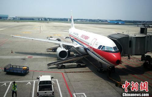 图为成都双流国际机场停机坪上正在上客的客机。(资料图) 中新社记者 刘忠俊 摄