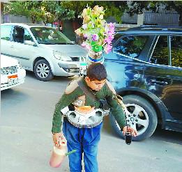腰间斜挎大水壶 负重二十多公斤 开罗少年插着玫瑰花卖水