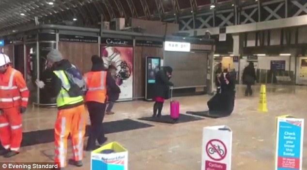 精致!英老妇耐心等待车站铺设防滑地毯 铺一段走一段