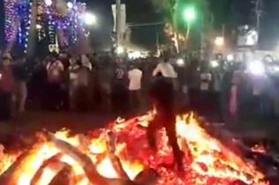 印度欢庆胡里节 男子驮孩子轻松蹚过燃烧灰烬