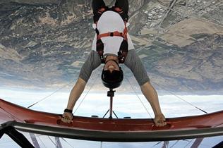 极限运动爱好者倒挂飞机机翼上表演高难度跳伞