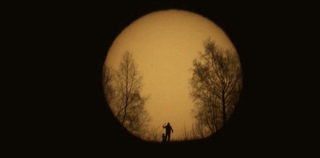 摄影师借望远镜拍到日出时分与爱犬玩耍剪影