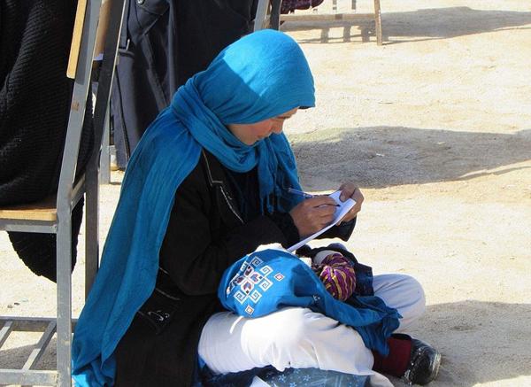 阿富汗一母亲抱娃席地而坐参加大学入学考试