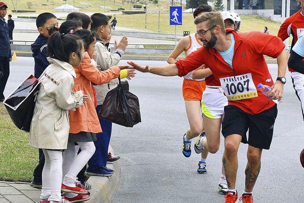 平壤举办国际马拉松赛 外国选手与朝鲜小孩互动