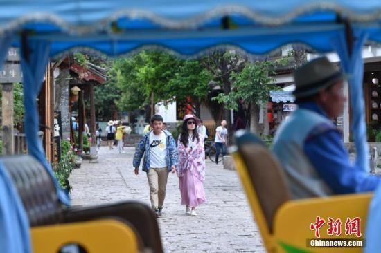 资料图:游客在丽江束河古镇内游玩。 中新社记者 任东 摄