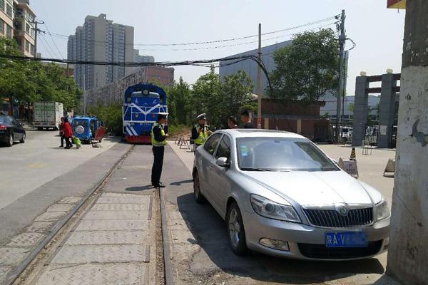 轿车停在铁道旁 火车被逼停堵了半个多小时