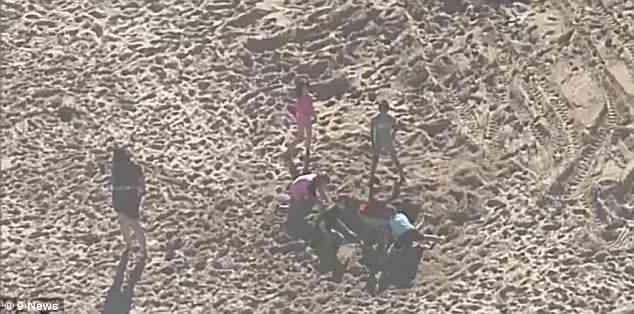 澳男孩海滩玩耍时陷入沙穴 好心人上演疯狂救援