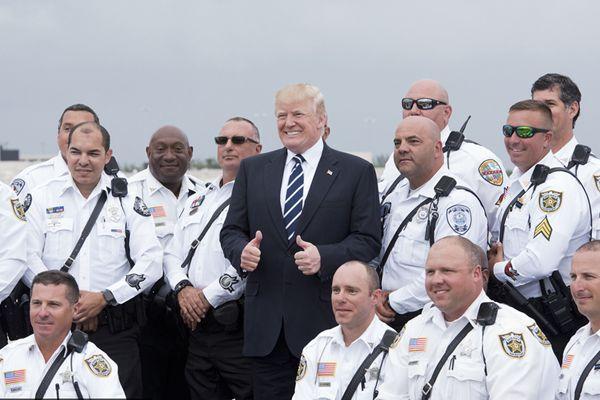 特朗普即将离开棕榈滩 机场与摩托车警员合影笑容满面