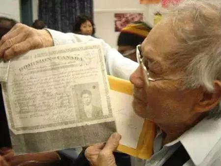 """加拿大华人手持其父1918年缴纳完""""人头税""""后获得的移民书证。"""