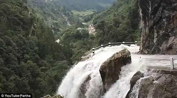 尼泊尔山路一侧瀑布一侧悬崖 旅游车惊险淌过