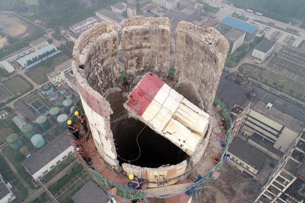 惊险!数名工人在180米高空徒手拆烟囱