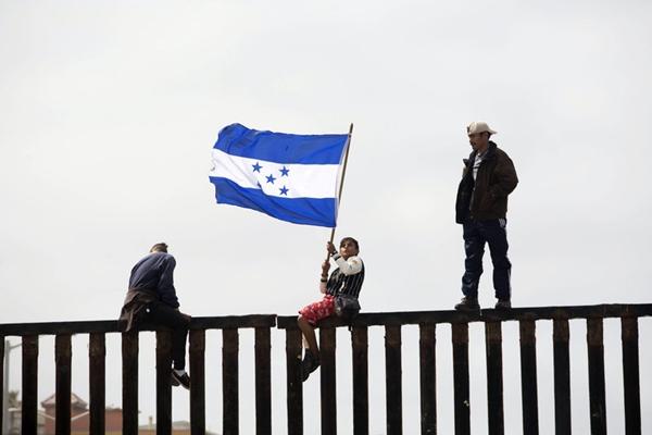 美墨边界举行边界集会 中美洲移民爬上边界墙