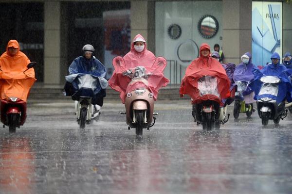 江苏扬州遭遇暴雨天气 市民冒雨出行