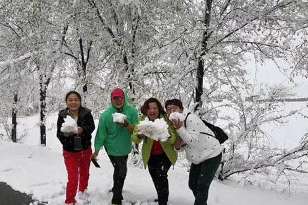 新疆天池白雪皑皑 游人戏雪如孩童