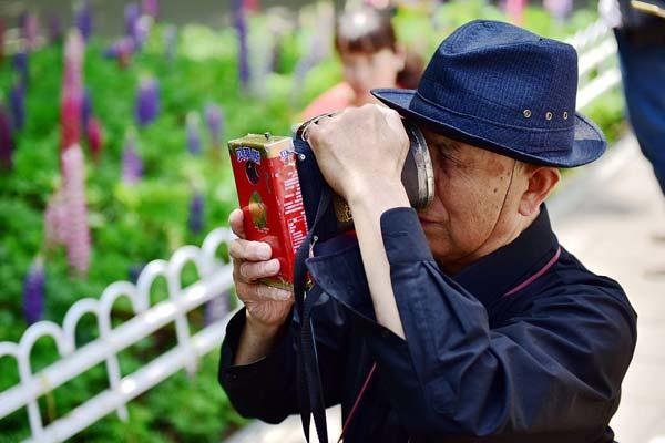 北京八旬老人自制数码相机 为来往游客免费拍照