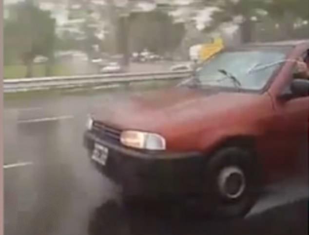 阿根廷司机一手开车一手拉绳子操纵雨刮器