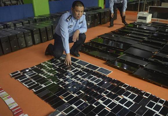 沈阳警方破获1.2亿网络诈骗案 涉案手机电脑铺满地面