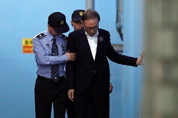 李明博涉贿案首次庭审结束 在狱警搀扶下离开法院