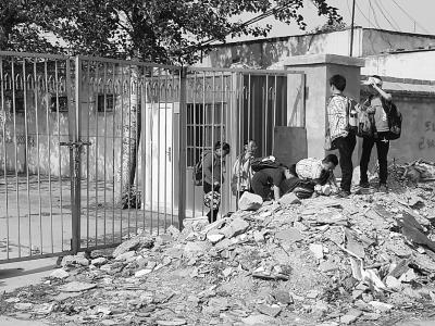 北京一村因拆迁砌墙封路 学校成孤岛学生翻墙钻洞