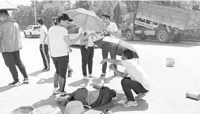 老人遇车祸躺在路中间 十几名年轻干部撑伞守候