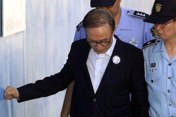 韩国前总统李明博体力不支 用拳头撑墙走进法庭受审