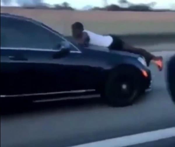 惊险!美国男子趴在飞驰中汽车引擎盖上