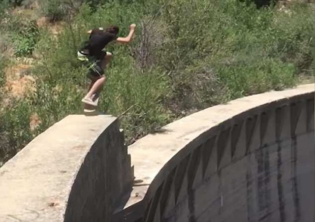 极限挑战!美男子在60米高坝顶展示滑板技巧