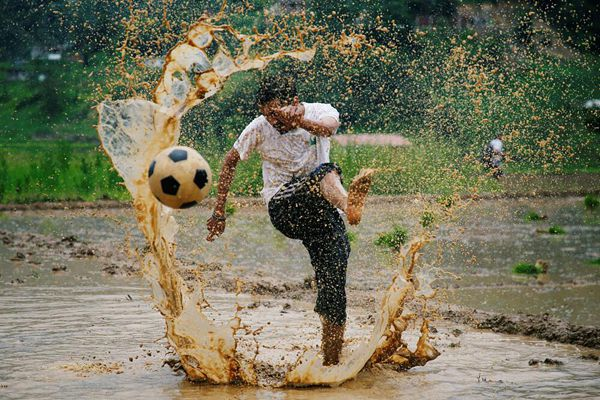 尼泊尔民众庆祝水稻日 田间踢球撒欢泥浆飞溅