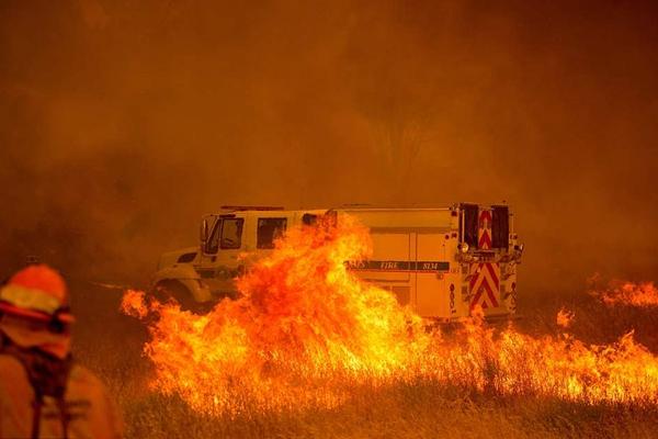美加州火灾持续蔓延过火面积达12150公顷 消防车被火光包围