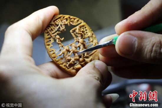 探访核雕艺人 方寸桃核上雕出迷你版世界杯