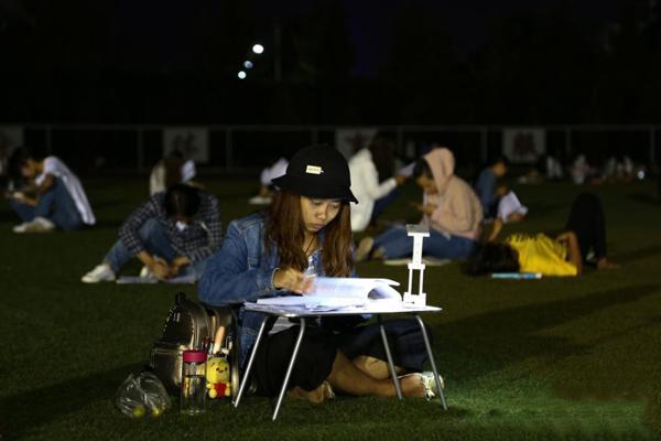 云南曲靖一高校学生夜间足球场边纳凉边复习备考