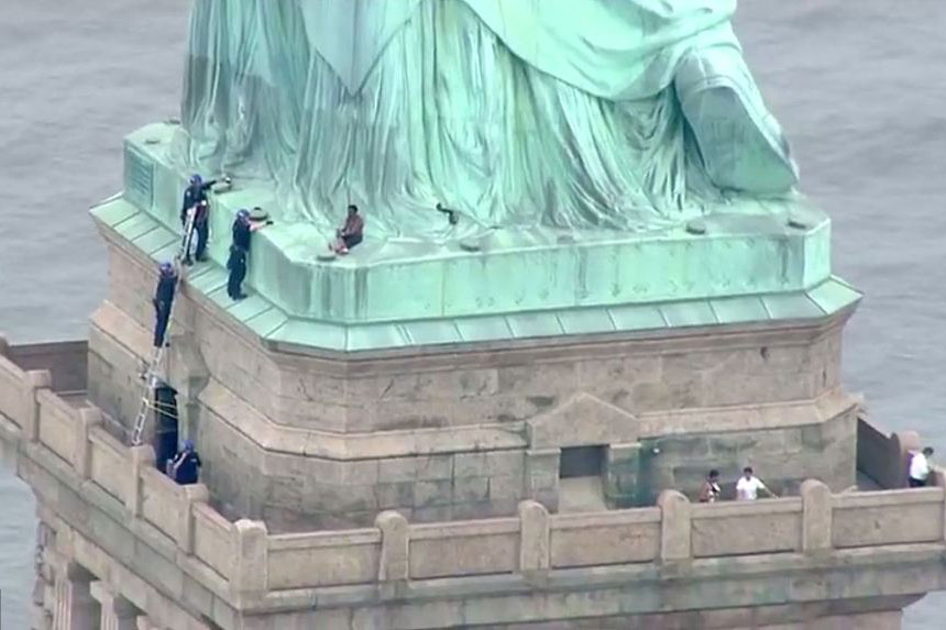 """向""""女神""""控诉!纽约一女子爬自由女神像示威警方劝阻"""