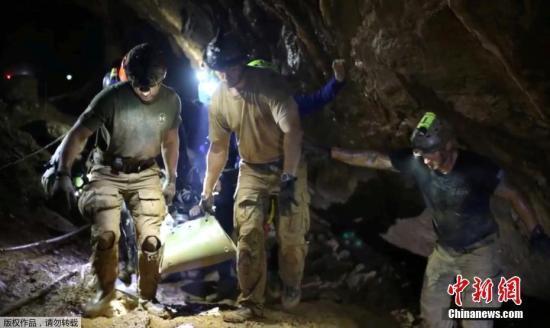 图为救援人员正在洞穴内穿行,执行救援任务。