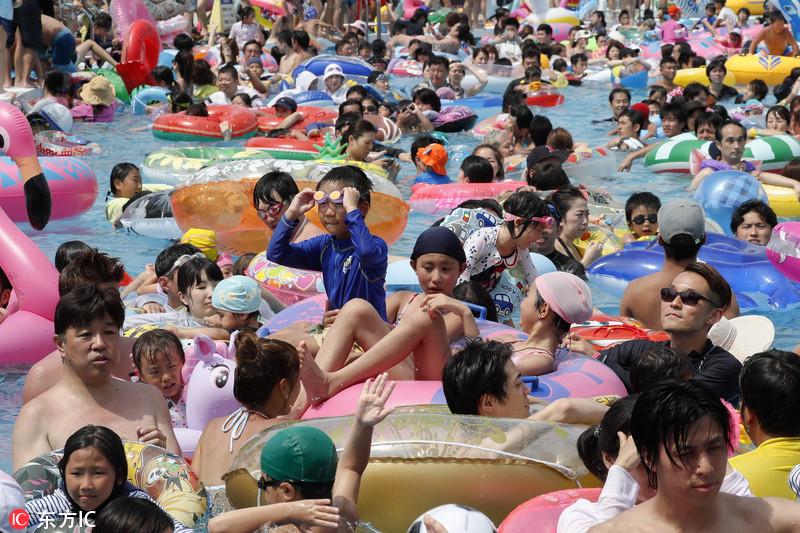 """东京遭高温袭击 民众在游乐园玩水""""下饺子"""""""