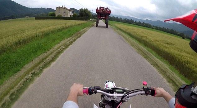 神勇!西班牙一青年骑摩托车从拖拉机下快速钻过