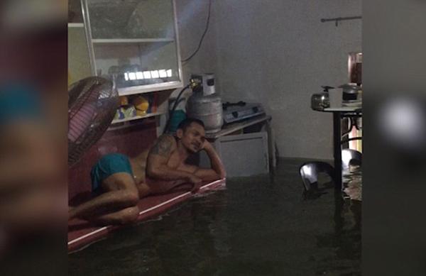 菲律宾男子洪水过后将漫水客厅当私人泳池